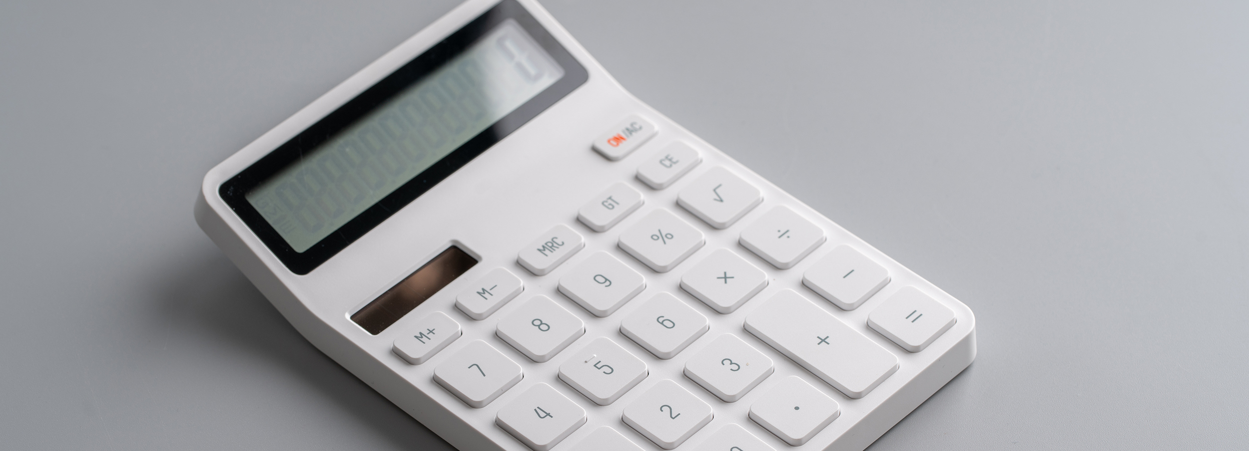 White calculator on grey background for education & business con